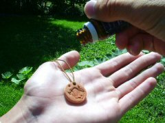 adding a drop of essential oil to a Terra Cotta Pendant